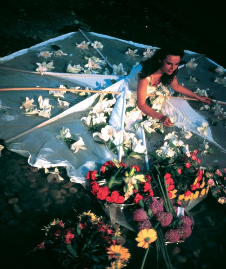 "Natura Viva.  Performance at Akademie der Künste, Berlin in 1995, was inspired by the tradition of still life, (Natura Morta). An expedition into a world of stories and poetry, dealing with vanity, the transitory nature of information, beauty, blooming, and aging, this piece is investigating the language of flowers. Frank slowly opened her white dress embroidered with 400 white lilies, reciting lines of poetry hidden in the surrounding blossoms, painting her face with pollen and speaking about blooming and wilting. In the end she freed her dress from its boning leaving it behind to ""drown"" in the pond."